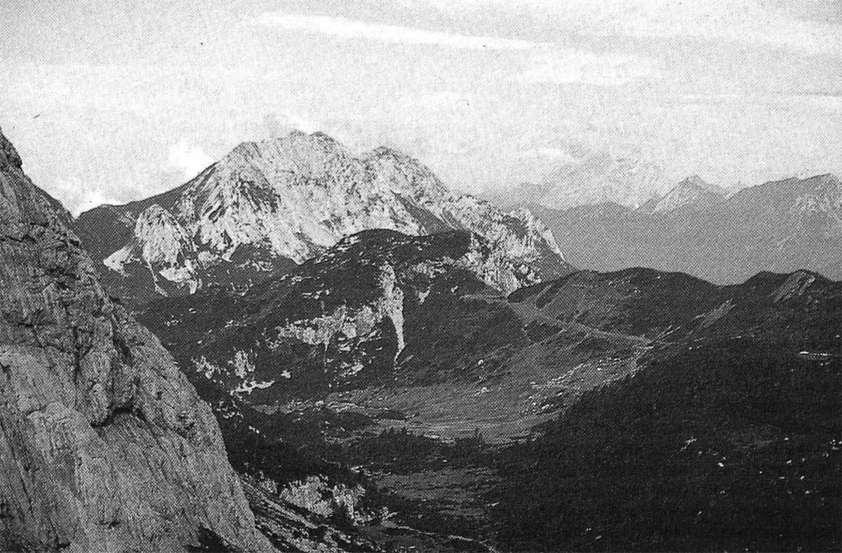 II pianeggiante fondo erboso della grande dolina che chiude, verso ovest, la Valle di Aip. Sulla sinistra si intravvede la ripida parete strapiombante della Creta di Rio Secco. In secondo piano si staglia il Monte Zermùla mentre sullo sfondo emerge il massiccio del Coglians.